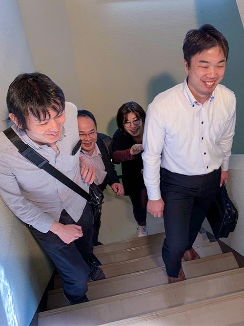 階段を登るスタッフ4名